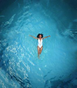 Девушка в закрытом белом купальнике лежит на спине в море, раскинув руки в стороны