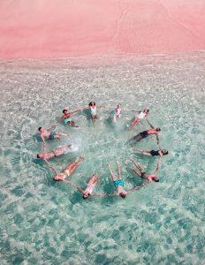 Двенадцать человек держатся за руки, лежат на воде на спине и образовали круг